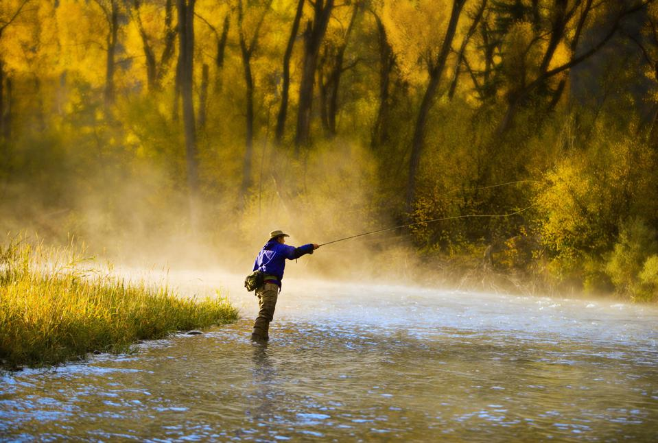 Male fly fisherman casting on the river.
