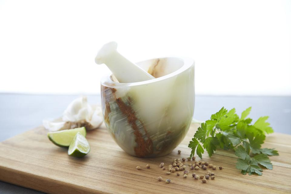 The Artisan Variety Small Onyx Mortar And Pestle on a wood board surrounded by spices and a lime