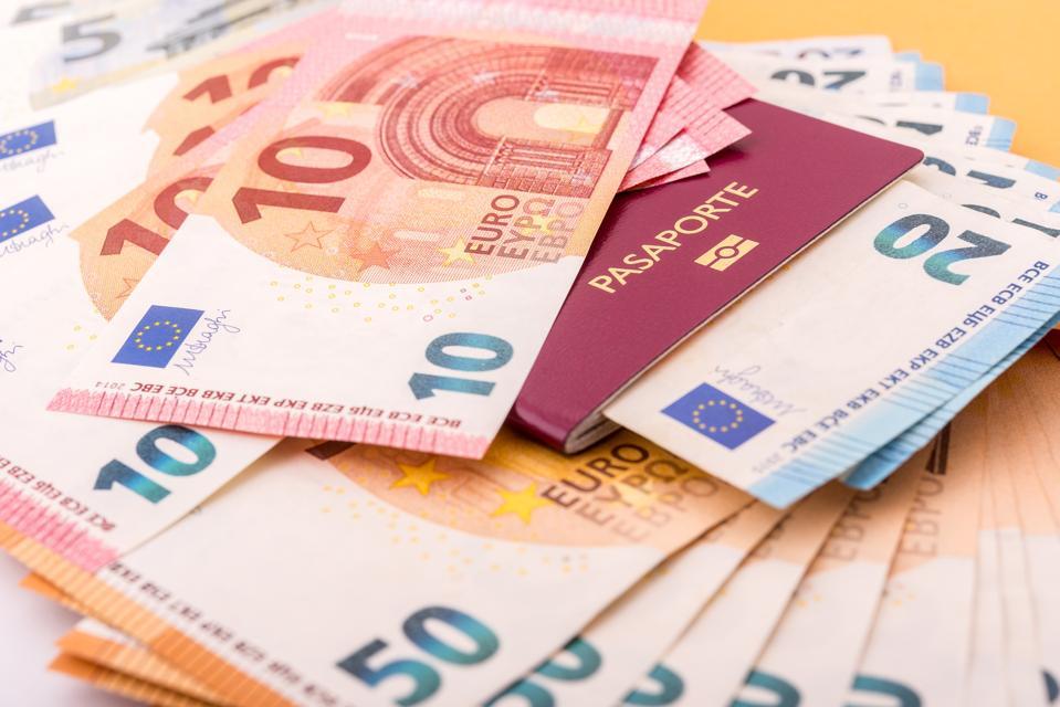A passport and  euro bills illustrating 'golden visas.'