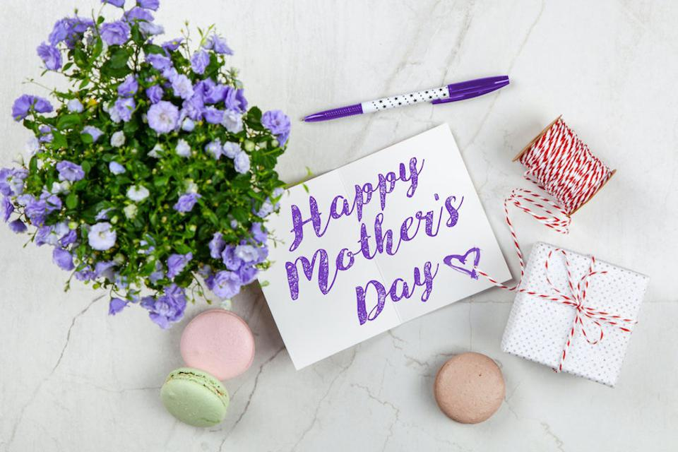 Mother's Day card, flowers and gifts on marble background