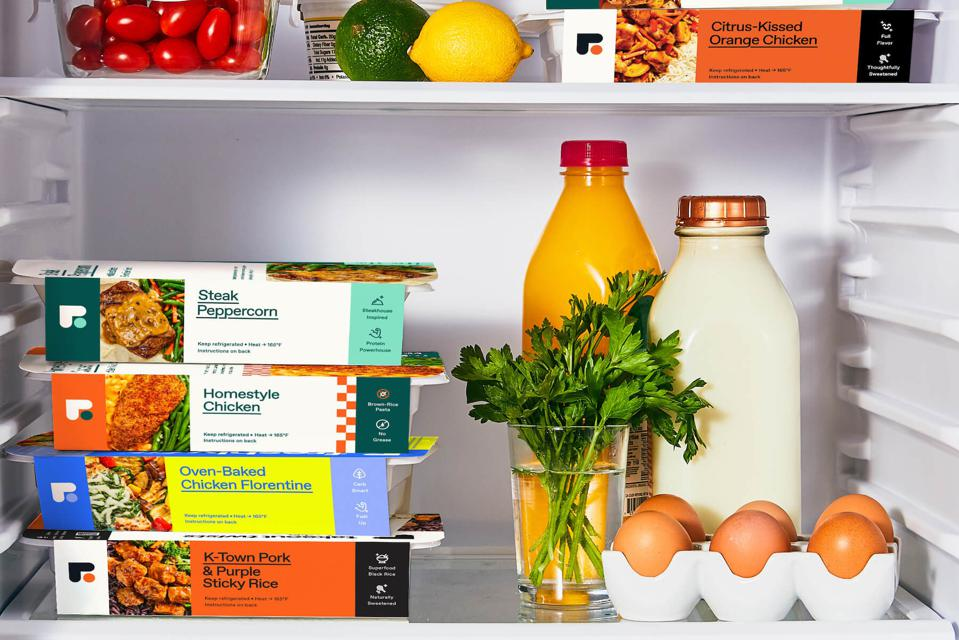 The inside view of a fridge with FreshlyFit meals stacked next to eggs and herbs.