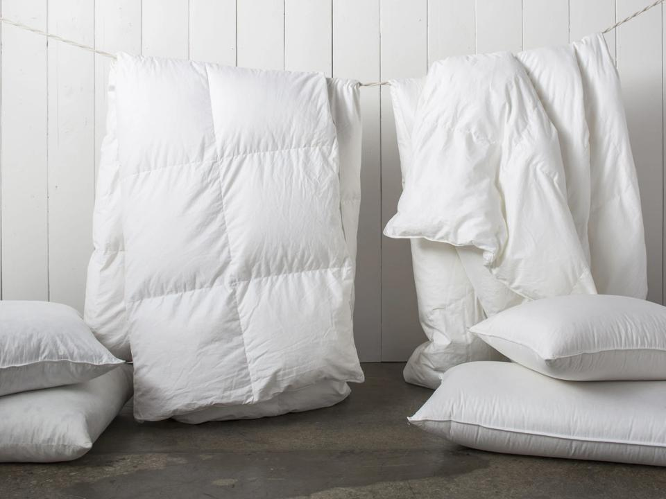Two white Parachute Down Comforters hung on a clothing line.