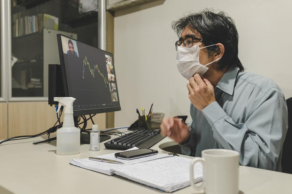 Worker alone in office adjusts his mask during a video conference with remote colleagues