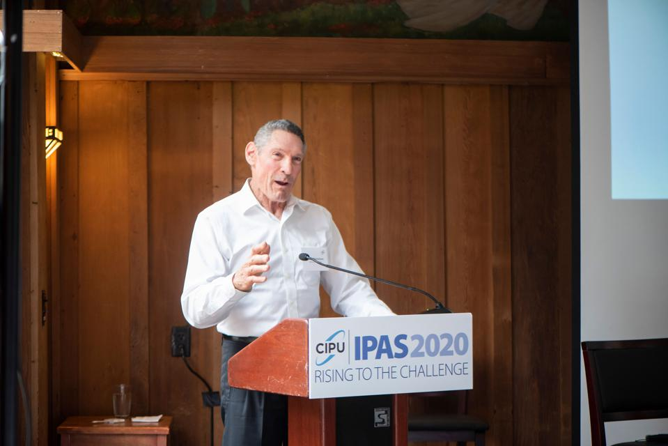 Man in a white collared shirt stands in front of podium in a wood paneled room