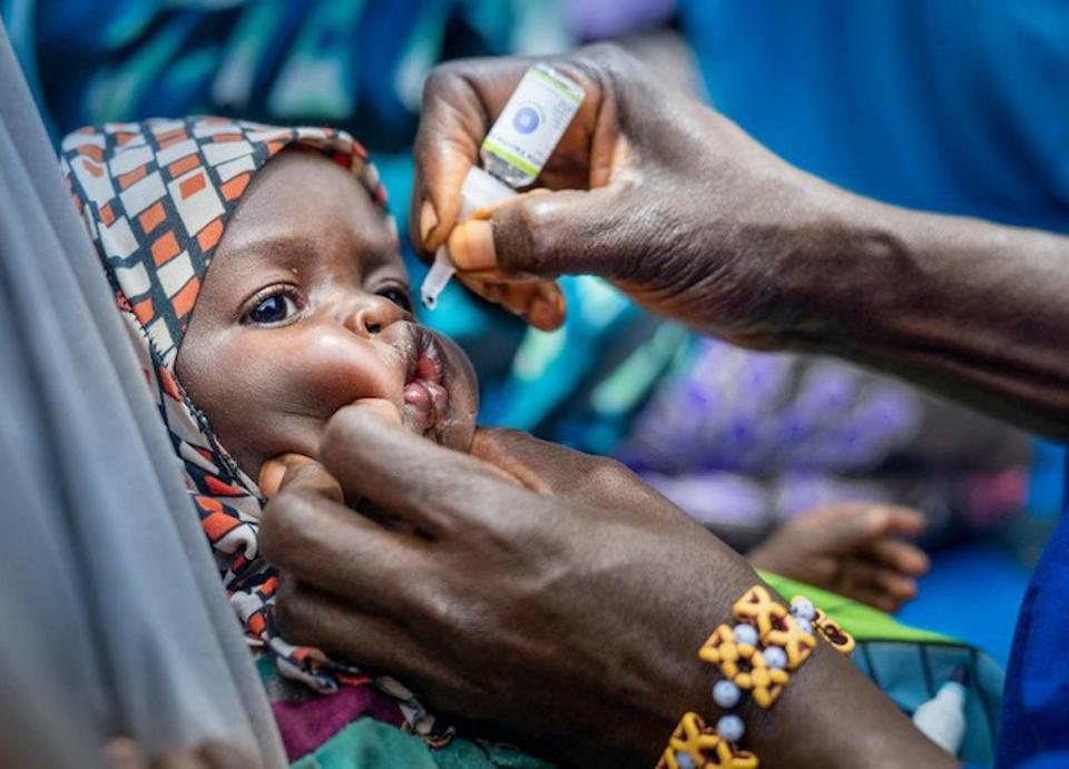 A volunteer community mobilizer (VCM) administers the oral polio vaccine to a child in Fanisau Ugongo Village, Kano State, Nigeria.
