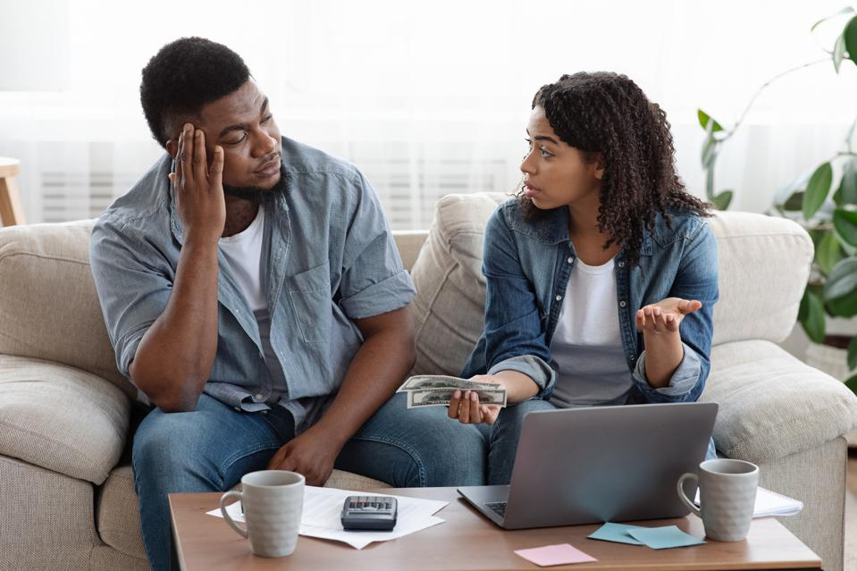 Couple accounting family budget at home, wife scolding husband for overspending