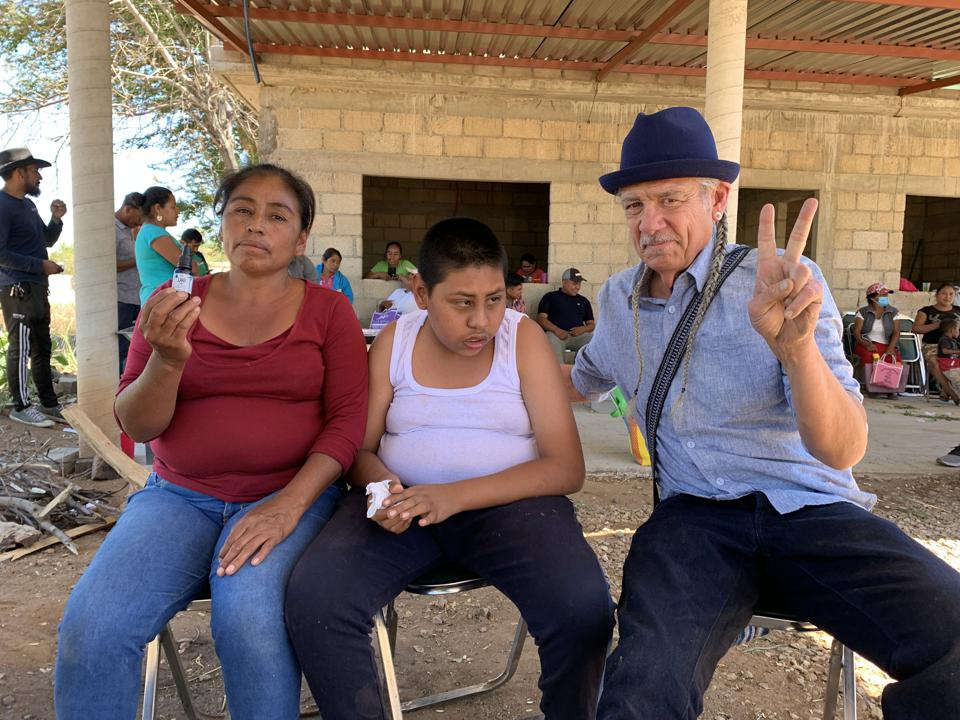 Cannabis activist Steve DeAngelo gives the peace sign while posing with residents of La Pe in Oaxaca, Mexico.