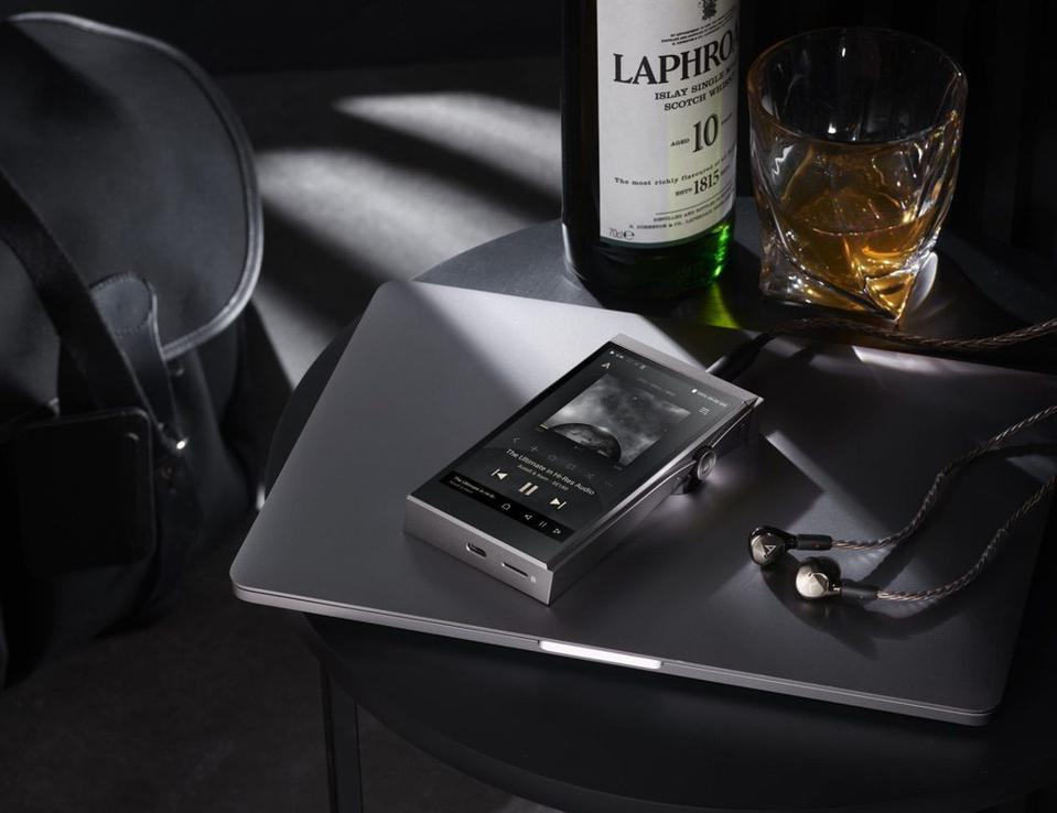 Astell&Kern AK-SE180 on a laptop with earphones and a bottle of whisky in the background