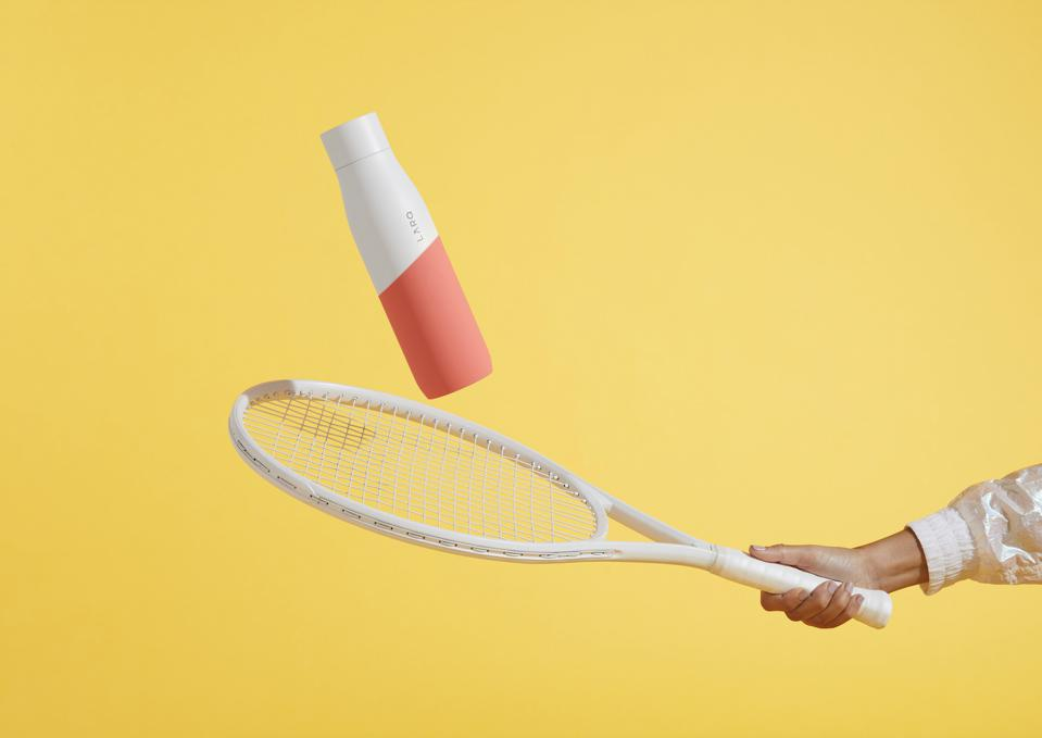 a white and coral coloured bottle bouncing on a tenis racquet