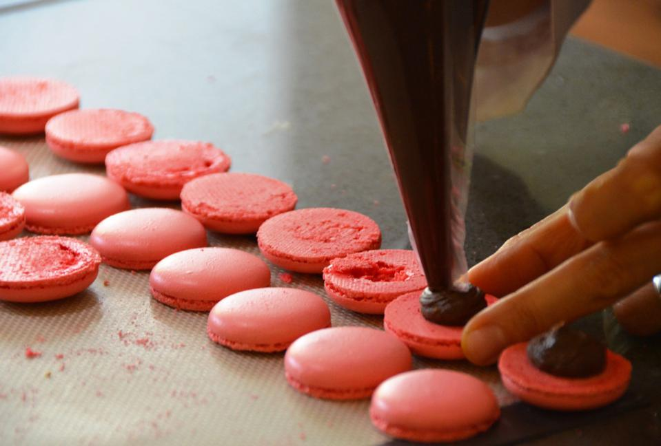 Piping Dark Chocolate Ganache on the shells of the cooled soft pink macarons is shown in this photograph from La Cuisine Paris.
