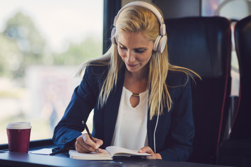 Professional woman listening to podcast with headphones; writing notes