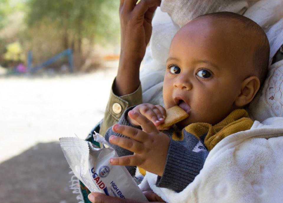 Natan, the youngest member of a family displaced by violence in Ethiopia's Tigray region, eats a high-energy biscuit.