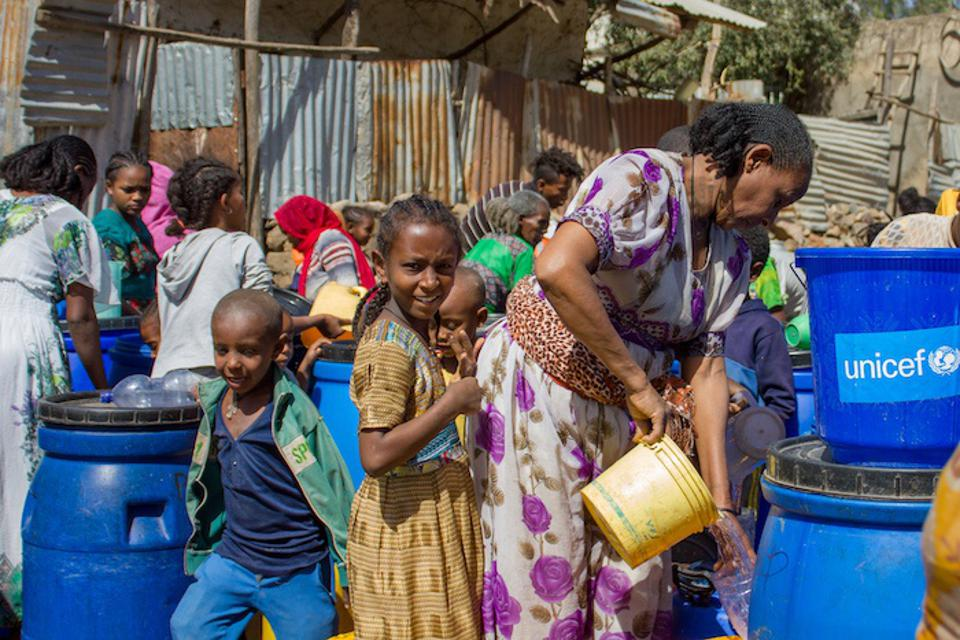 A family collects water at a distribution point outside a secondary school in Shire, Ethiopia.