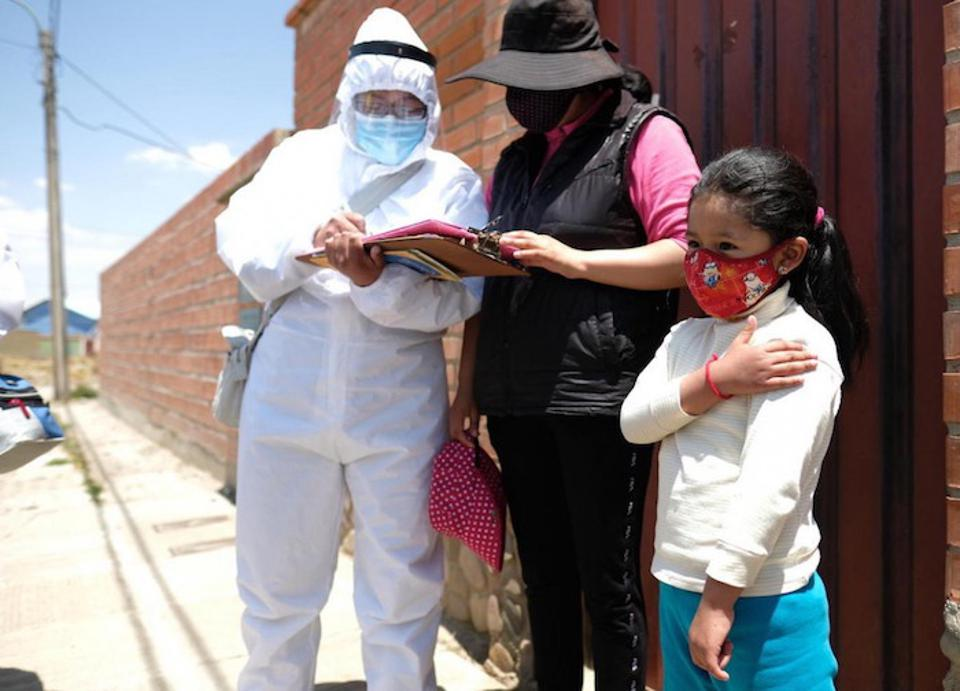 In El Alto, Bolivia, 6-year-old Noelia gently touches her arm after receiving a flu shot from a member of a UNICEF-supported vaccination team that goes door-to-door in the community, reaching children with lifesaving immunizations and micronutrients.