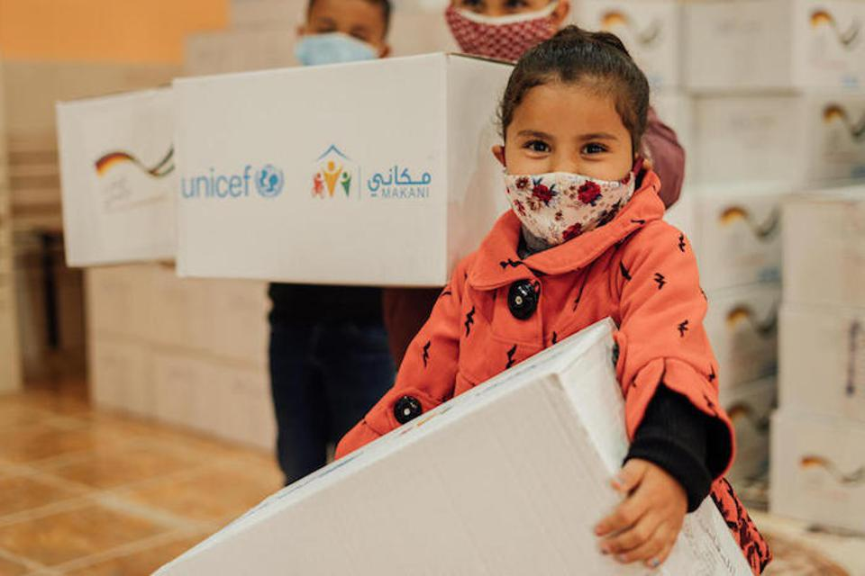 Four-year-old Lara holds a box containing warm clothing distributed by UNICEF at Makani Centers in Jordan.