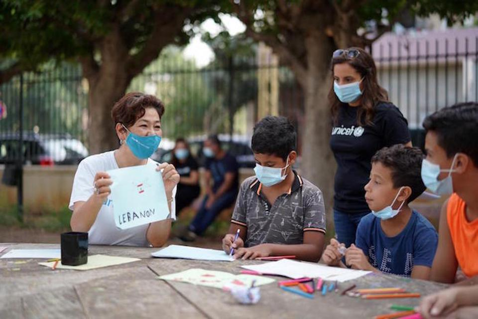 Children and UNICEF volunteers, all wearing masks to prevent the spread of the novel coronavirus, talk and draw in a park in Beirut, Lebanon.