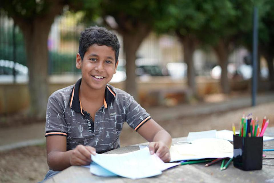 Hussein, 12, smiles, sitting at a picnic table covered with art supplies in a park in Beirut, Lebanon.
