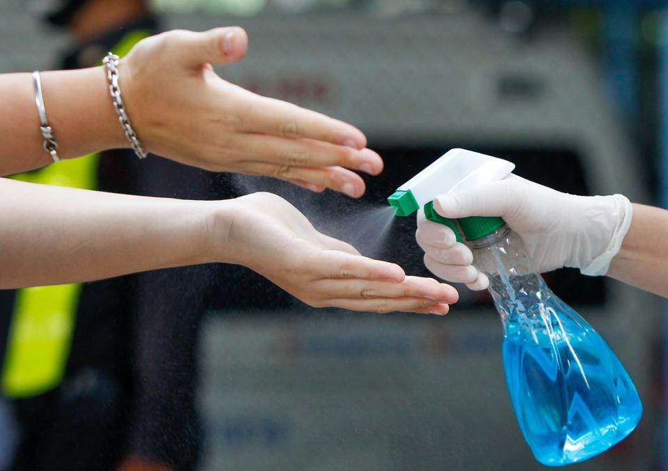 A health worker sprays a hand sanitizer to a woman as she...