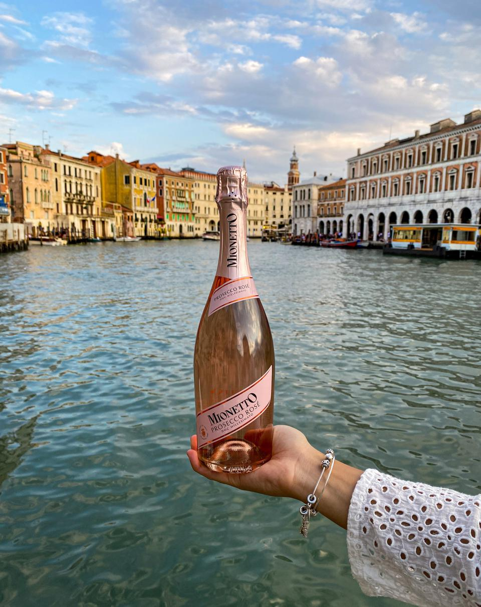 Bottle of Mionetto Prosecco Rosé Millesimato held aloft on Italian canal