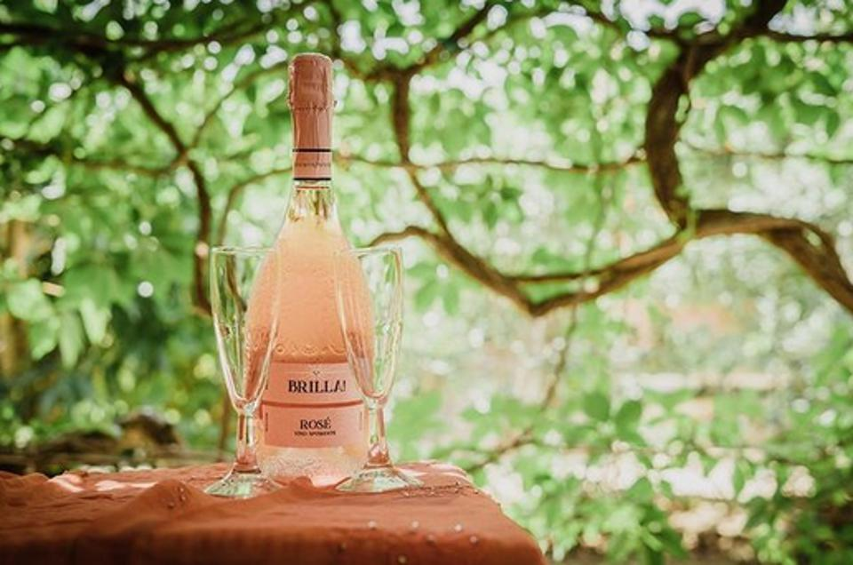 Bottle of Brilla Prosecco Rosé DOC with 2 flutes on an outdoor table