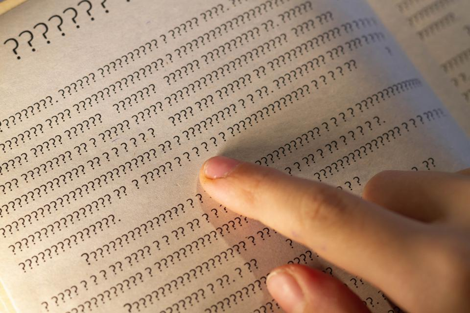 A person leads a finger on the lines in the book, but instead of letters only question marks on the page in the textbook