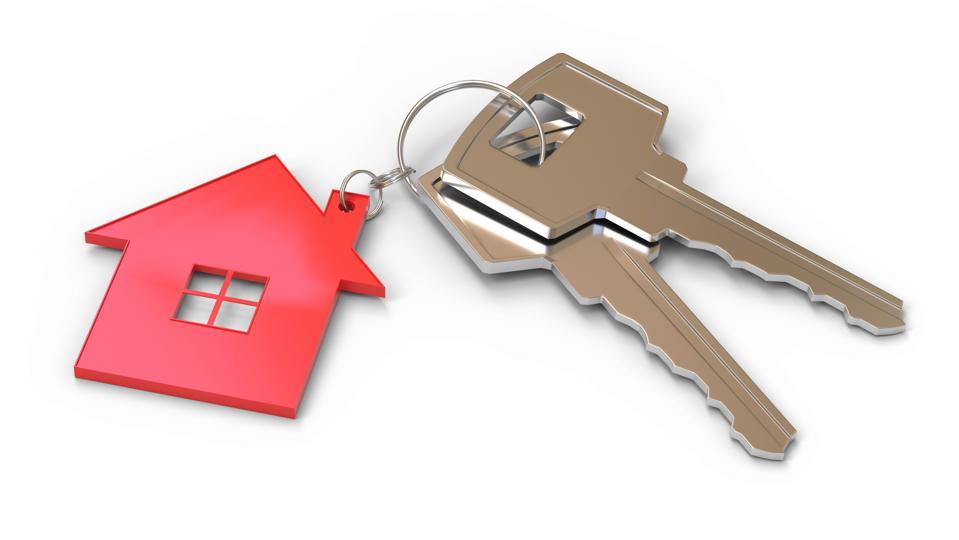 To house keys on a keychain shaped like the outline of a house