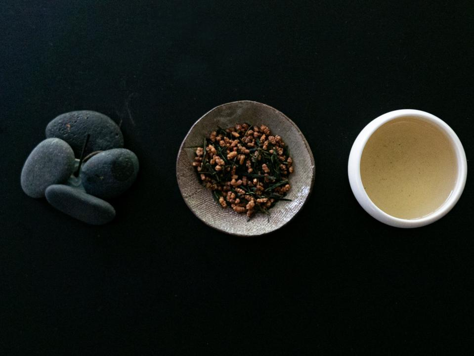 A pile of stones, a bowl of tea leaves, and a cup of tea on a black background.