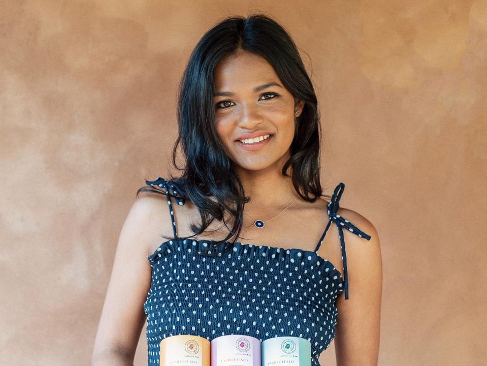 Chandra with long dark hair and blue sundress holding 3 canisters of Tea Drops.