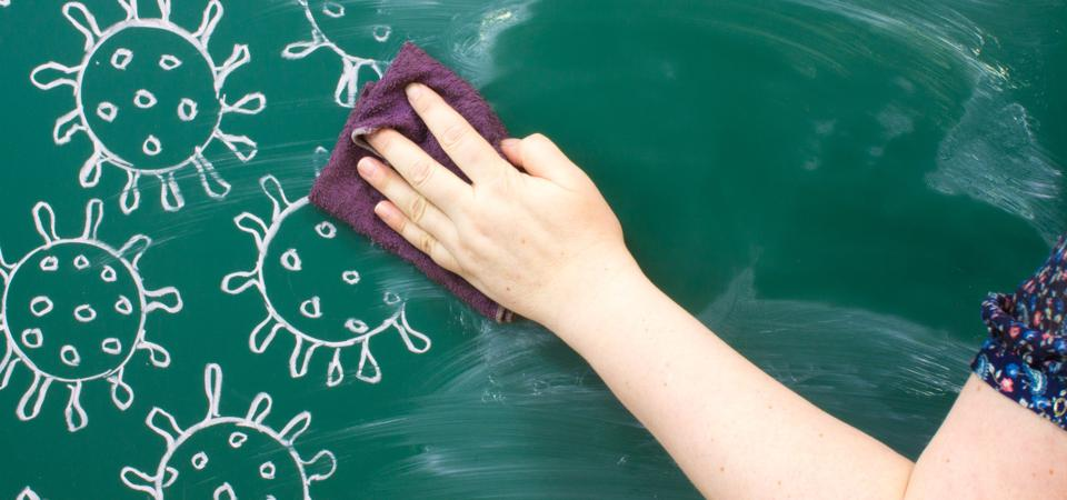 drawing on a green blackboard - close-up of coronavirus molecules and hand washing with a rag