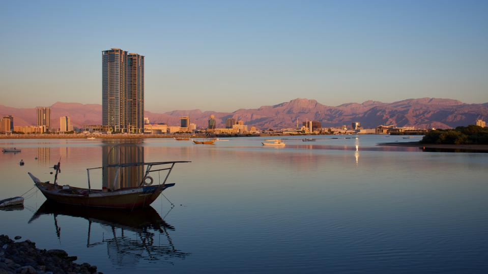 In the background are red mountains and a few buildings, including a tall skyscraper. Most of the photo is a calm waterway. There an old boat in the foreground.