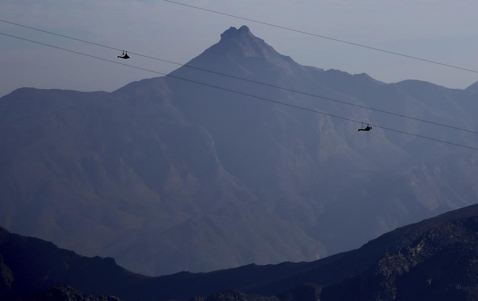 Two people zipline face down with a grey rocky mountain in the background.
