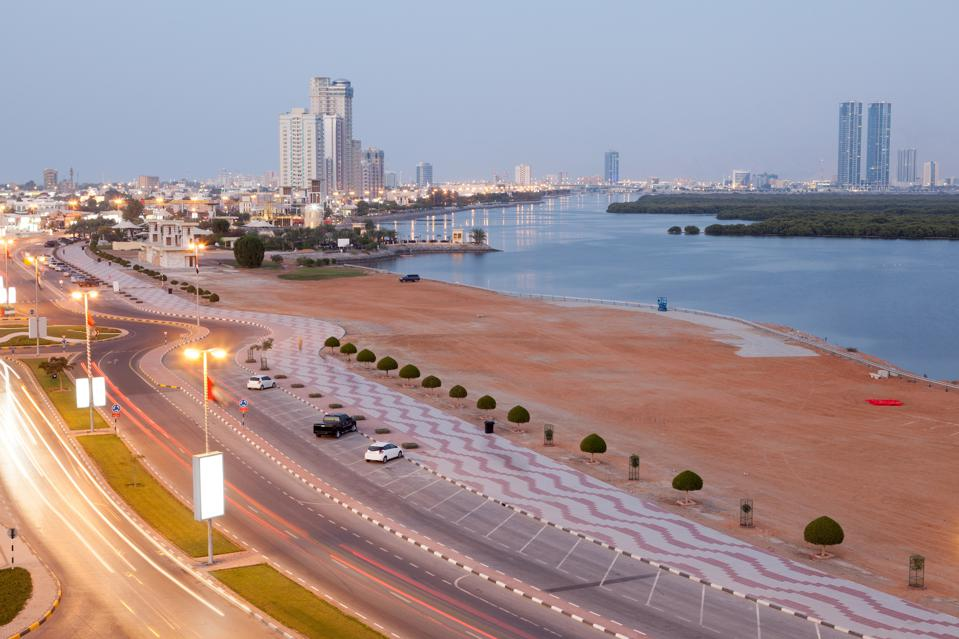 A waterway with city buildings and a few skyscrapers, a desert-like beach and a highway.