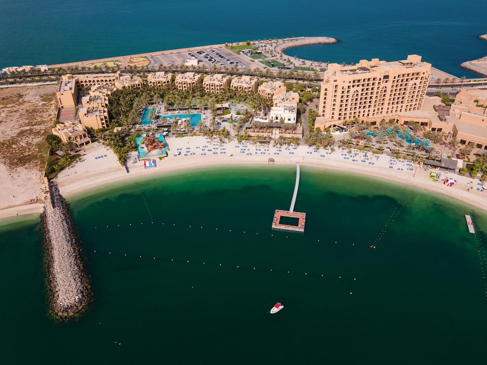 Aerial view of a strip of sand with hotel buildings and palm trees, with deep blue water on one side and a beach and water showing reefs below on the other