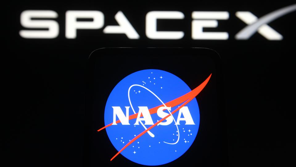 In this photo illustration a SpaceX and NASA (National...