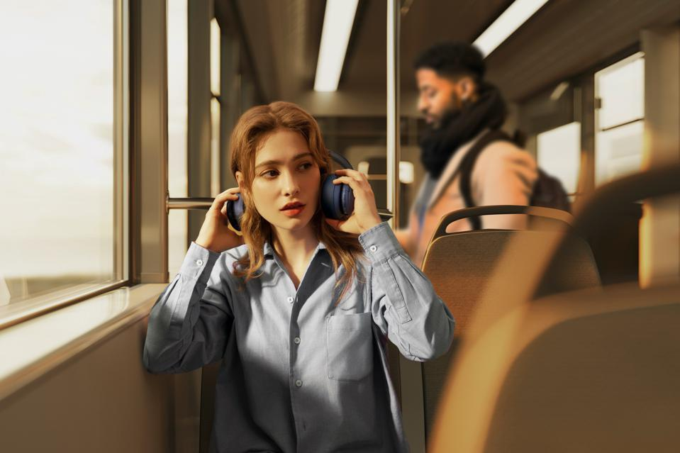 Woman on a train taking Soundcore Life Q35 headphones off