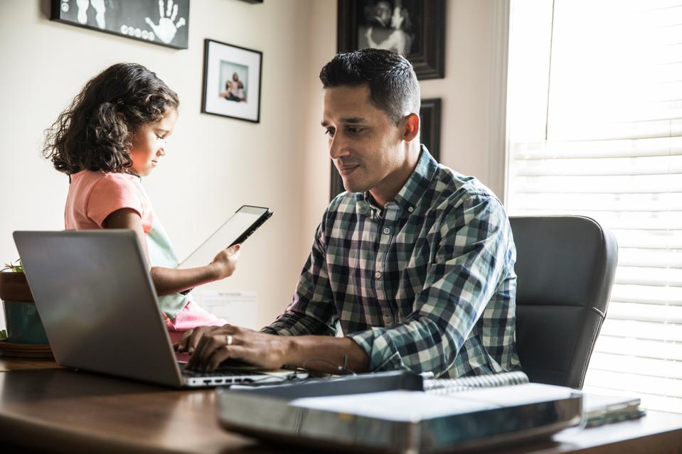 Father working at home with young daughter