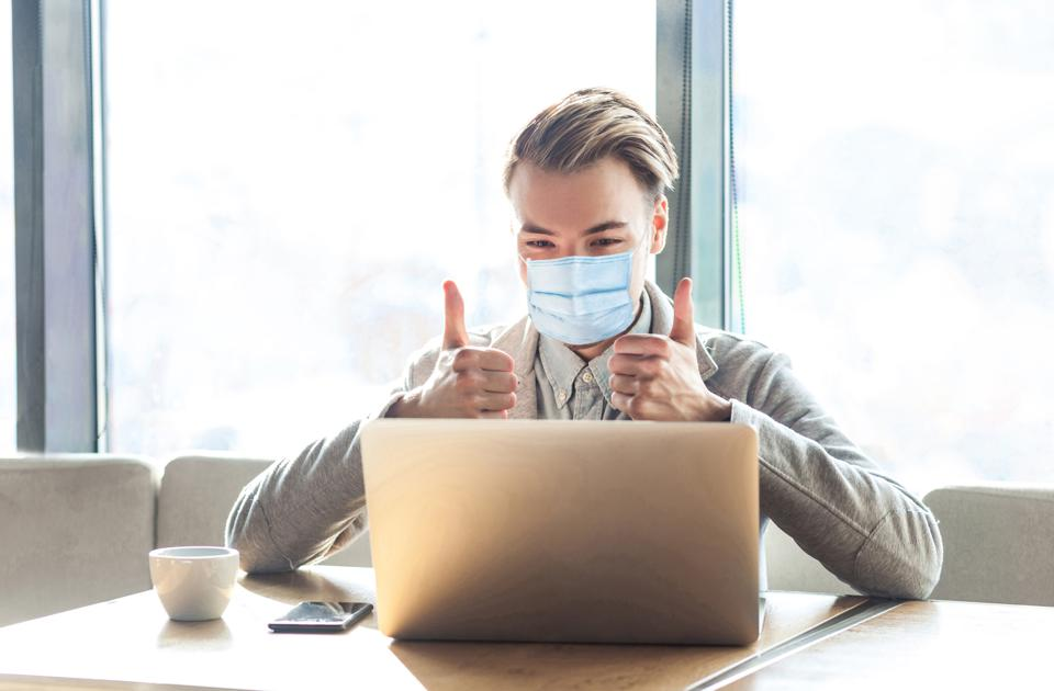 Working at home safe in quarantine time. Young satisfied man with surgical medical mask, sitting, looking at laptop screen with thumbs up.