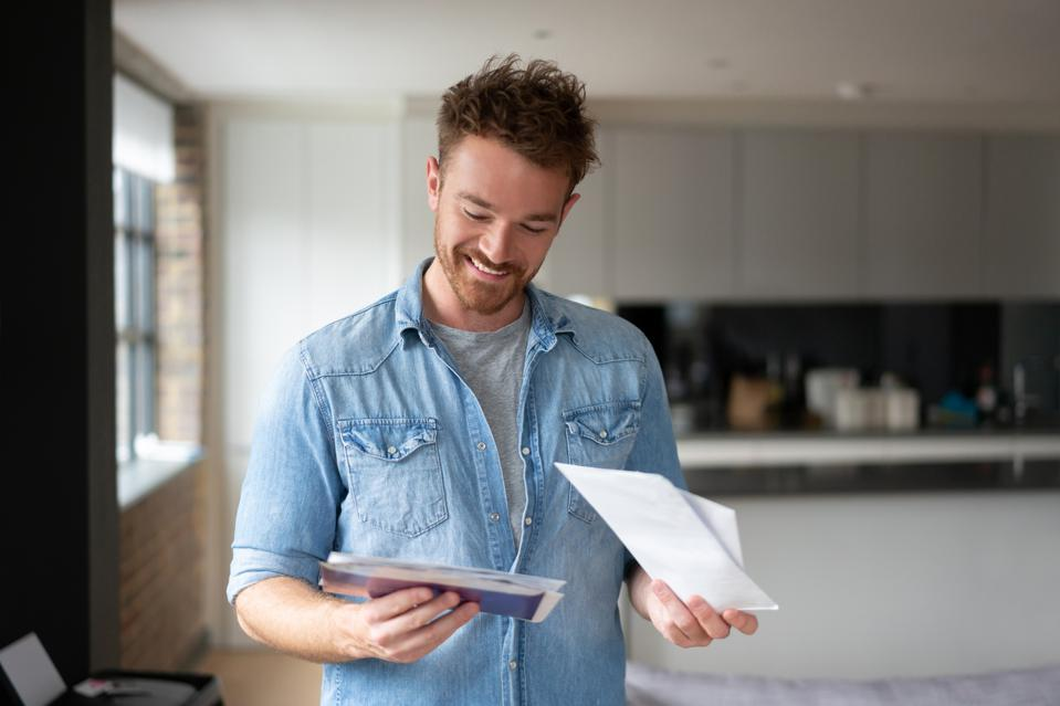 Happy man at home checking the mail