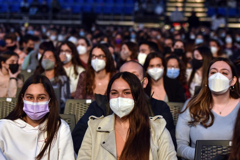 A group of people wearing face masks attend the performance...