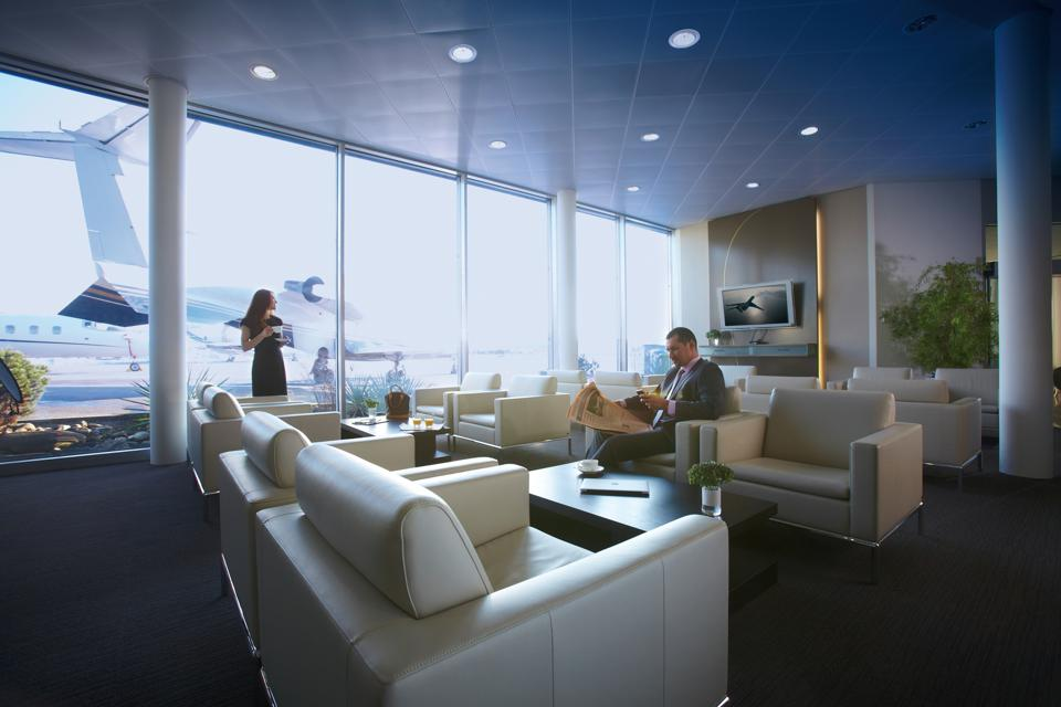 Two guests relax in Luxaviation's sleek private lounge in Zurich.