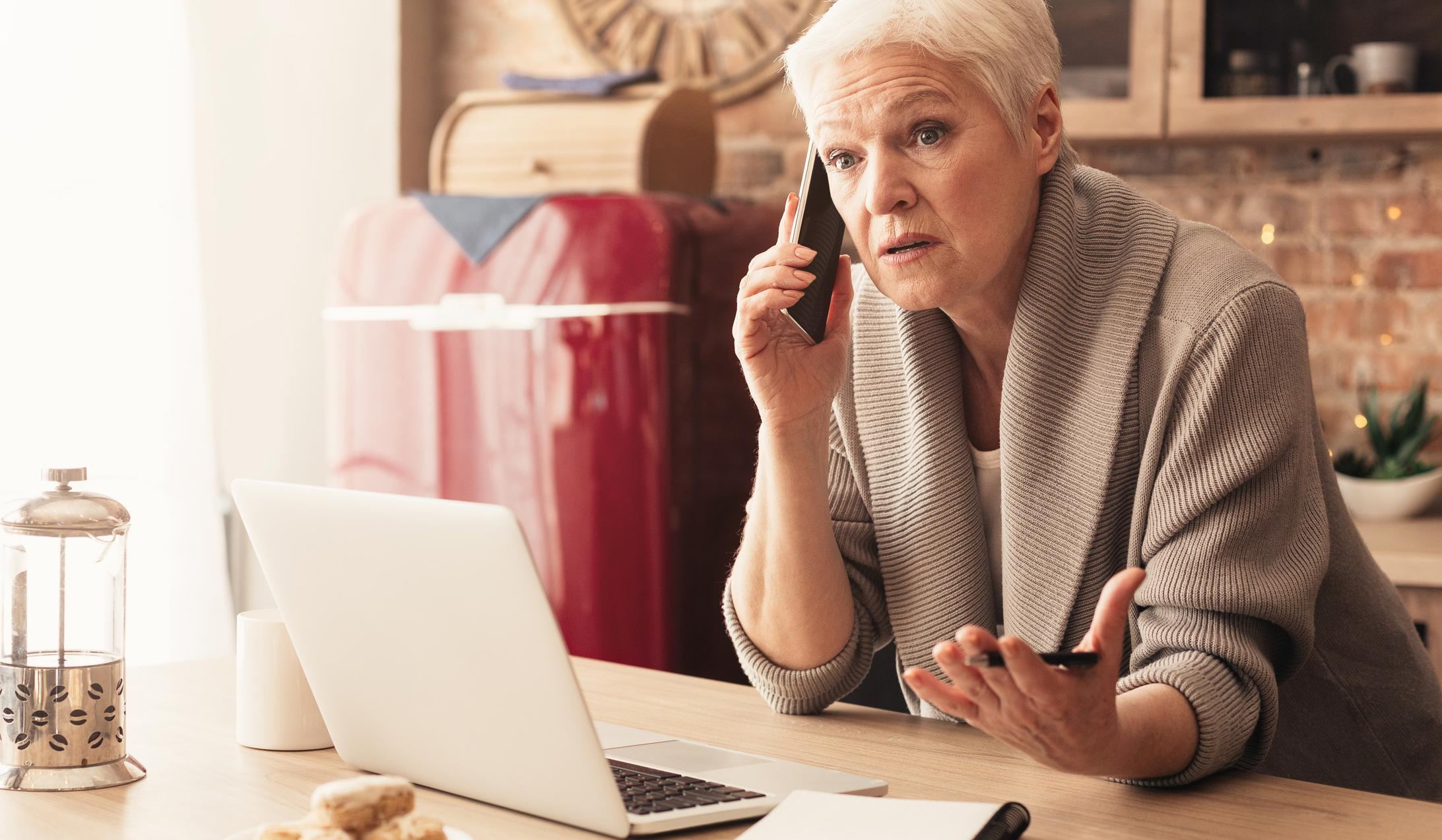 Concerned elderly woman talking on cellphone, working on laptop in kitchen