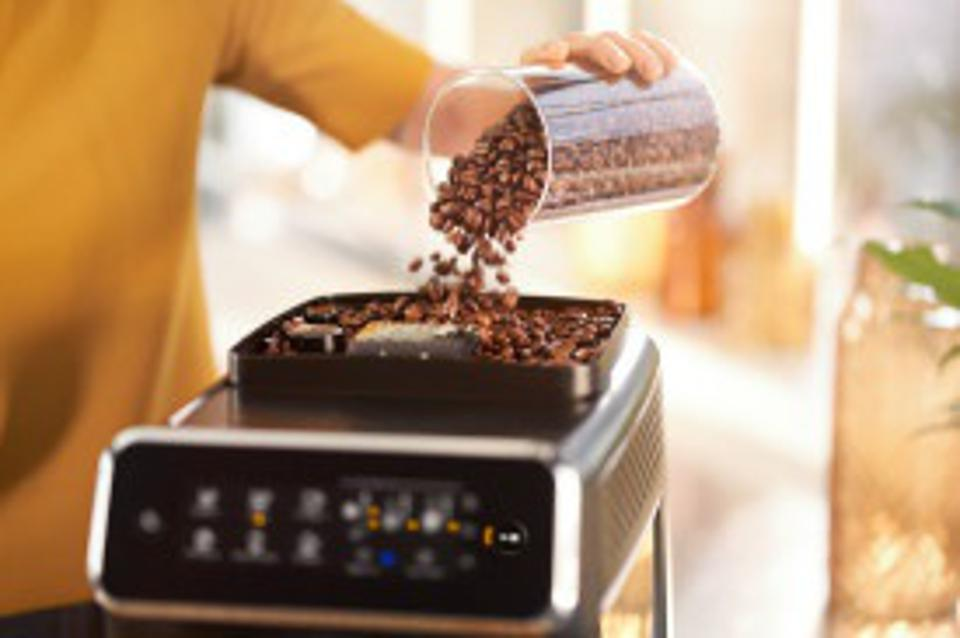 A woman pours whole coffee beans into the Philips 3200 machine.