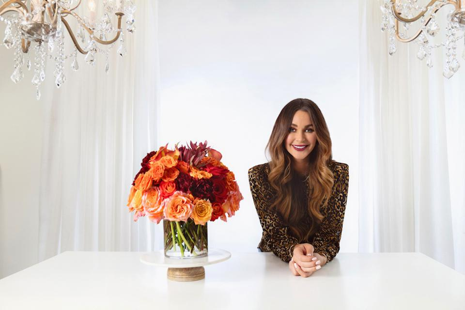 A brunette women stands next to a vase of roses in a white room.