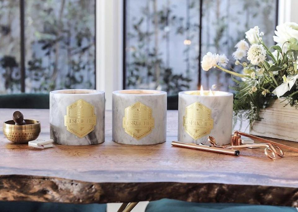 Three LesRuches Gardenia Beatué Mabré Candles on a table with candle scissors by a window.