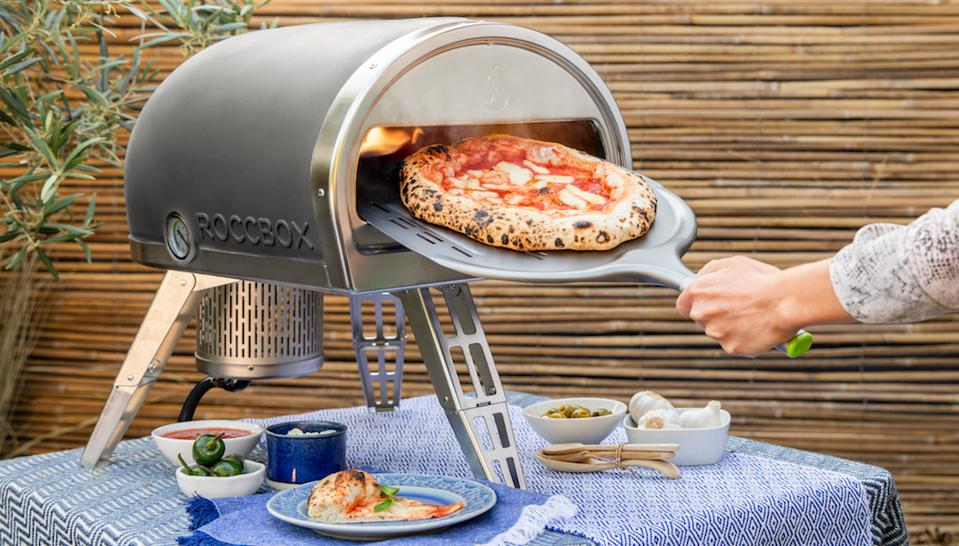 Gozney Roccbox Portable Pizza Oven on a table outside with a hand holding a pizza tray