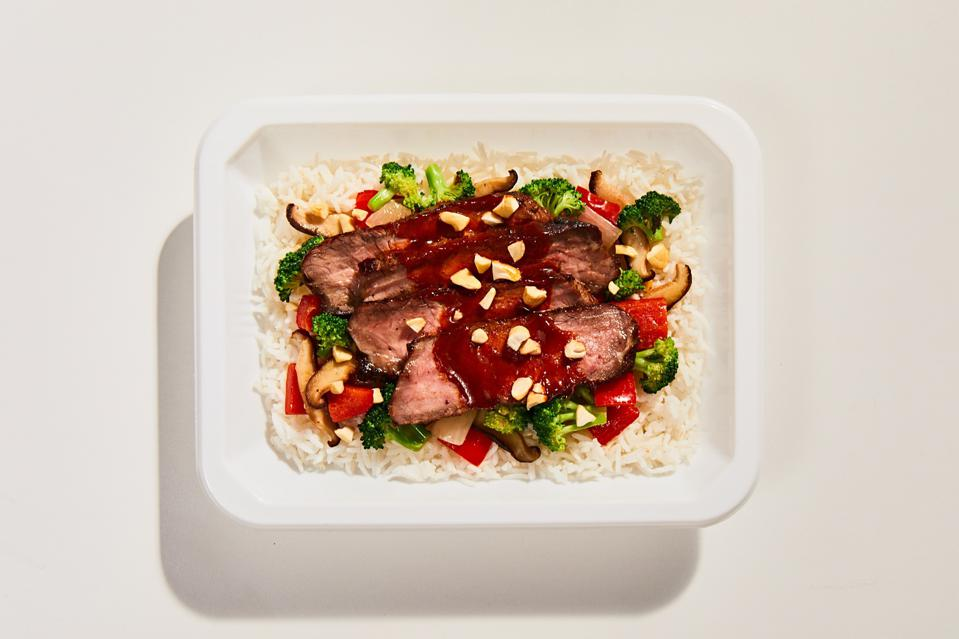 a tray filled with rice, steak and veggies made by the celebrity chef