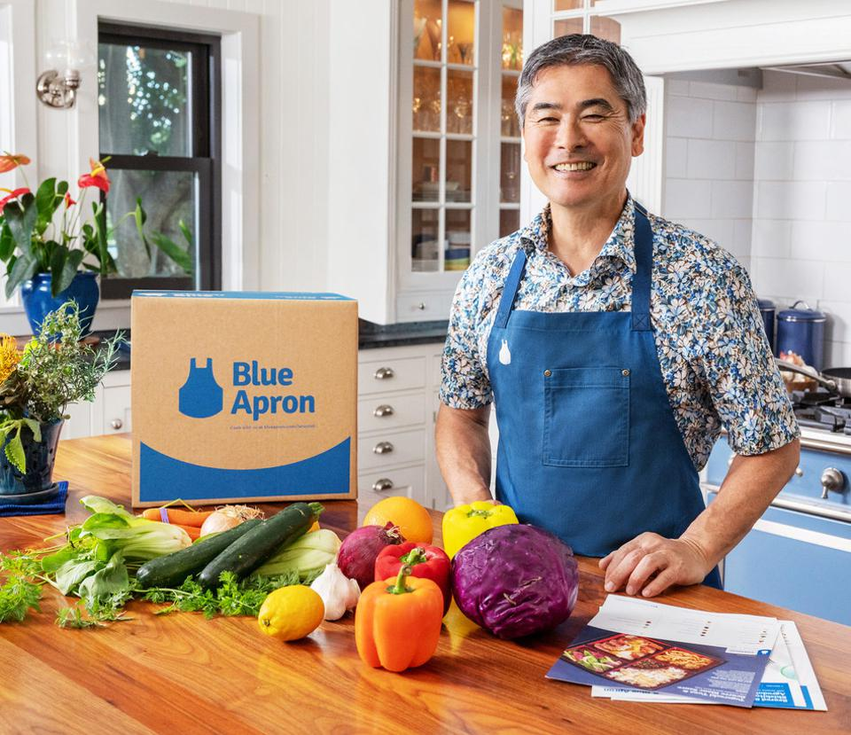 chef Roy Yamagachi in front of a Blue Apron box with assorted vegetables