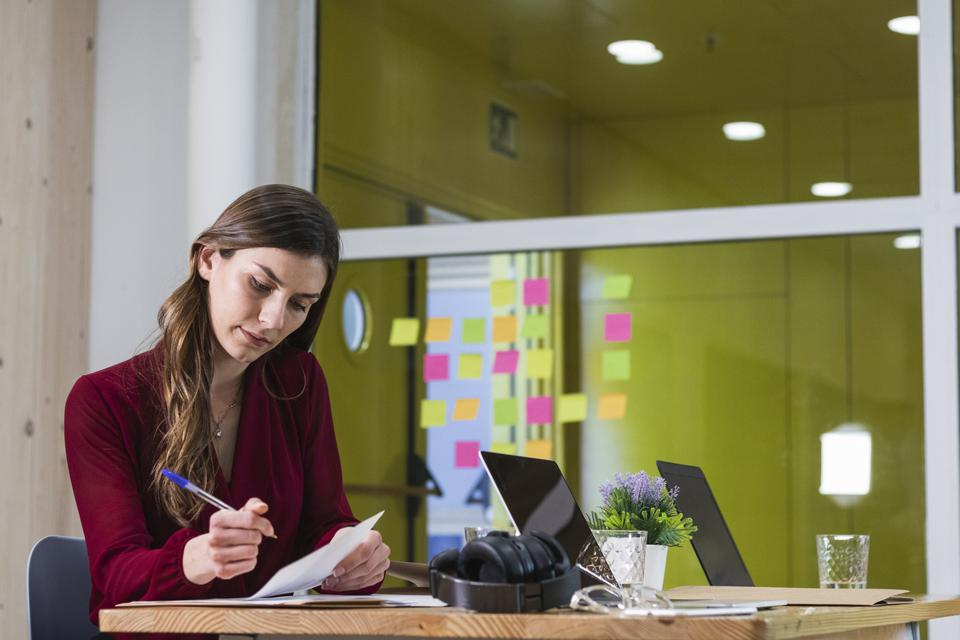 Young female entrepreneur working by desk at workplace