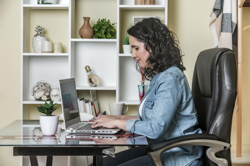 Adult female freelancer working on laptop at home
