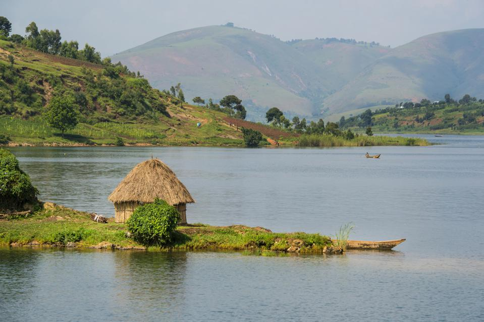 A thatch hut is in the foreground of this lake view with green hills